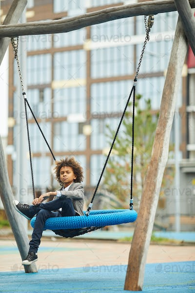 African boy resting on the swing