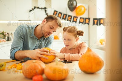 Family with pumpkins sitting at home