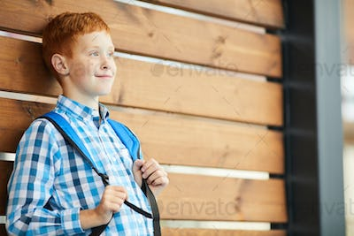 Schoolboy with packpack standing outdoors