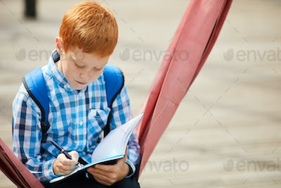 Schoolboy doing homework outdoors