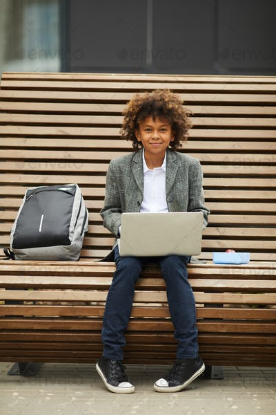 African schoolboy with laptop on the bench