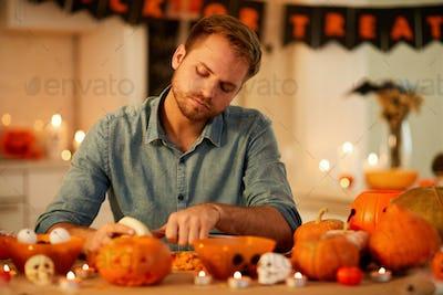 Young man carving pumpkin