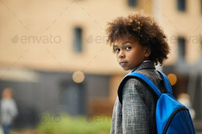 African schoolboy with backpack outdoors