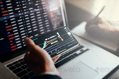 stockbroker using phone and laptop for profit gain analysis workplace