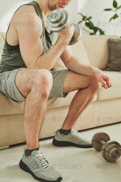 Young athlete in activewear holding metallic dumbbell while exercising on couch
