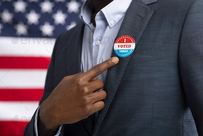 African American US resident showing with finger on inscription I voted today