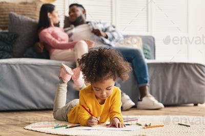 Couple on couch and daughter drawing on floor