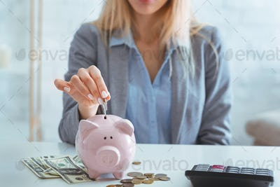 Girl puts coin piggy bank, near cash and calculator