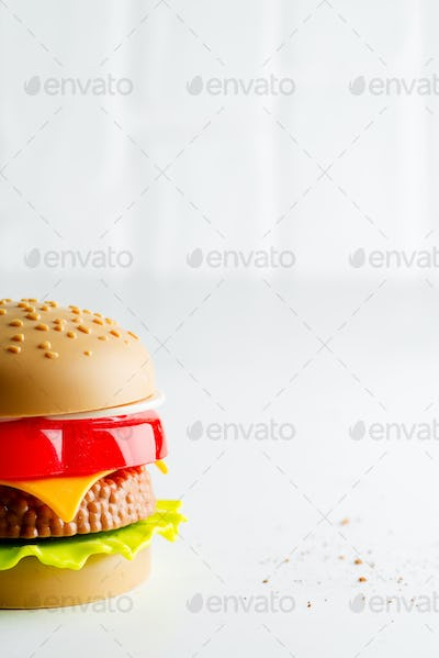 Artificial plastic burger with meat cutlet, tomatoes slice and green salad on a light grey