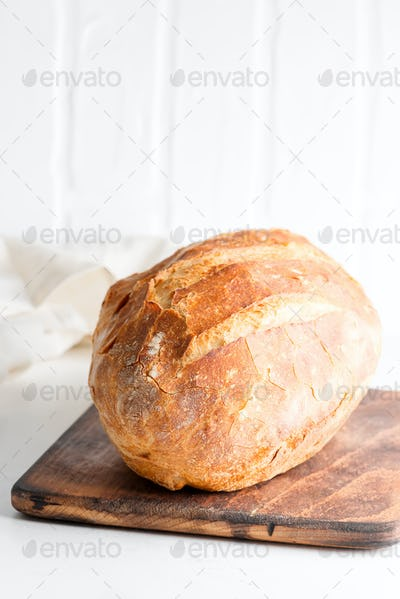 Homemade freshy baked bread on a wooden board and light grey marble table decorated textile towel