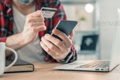 Freelancer shopping online with smartphone app and credit card