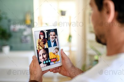 Unrecognizable man having video call on tablet at home