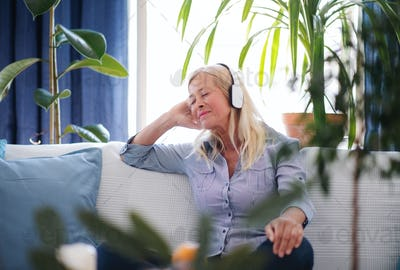 Attractive senior woman with headphones sitting indoors on sofa, relaxing