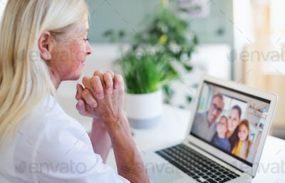 Senior woman with laptop indoors at home, family video call concept