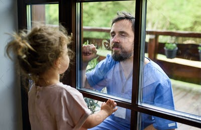 Doctor coming to see daughter in isolation, window glass separating them