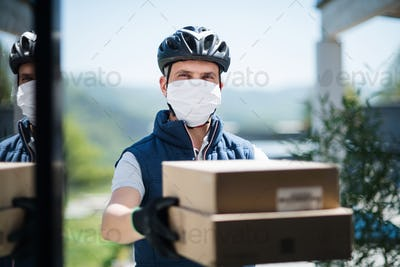 Courier with face mask delivering parcel, corona virus and quarantine concept
