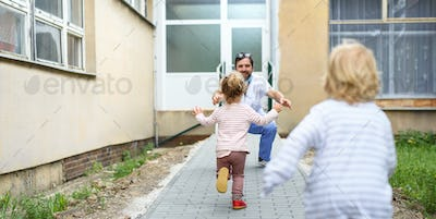 Children running to greet father doctor in front of hospital, end of coronavirus