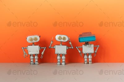 Three metal silver robots on peach colour background