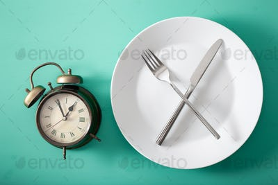 intermittent fasting, ketogenic diet, weight loss. fork and knife crossed on a plate and alarmclock