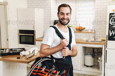 Image of plumber man smiling and holding bag with equipment in apartment