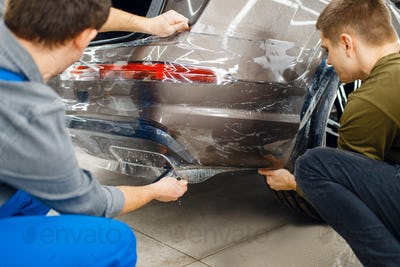 Two workers applies car protection film on bumper