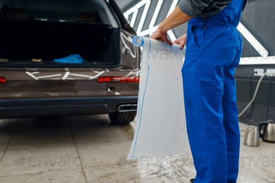 Male worker holds roll of car protection film
