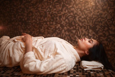 Woman lying on a hot stone, turkish hamam, sauna