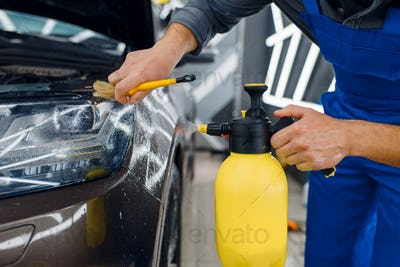 Worker cleans car surface with spray and brush