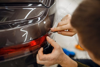 Specialist cuts car protection film on bumper