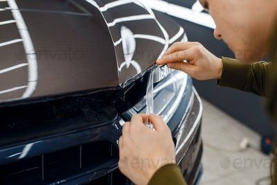 Worker cuts protection film on car hood