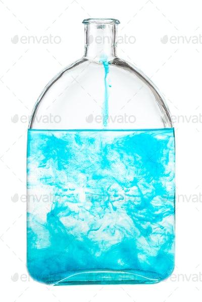 blue watercolour dissolves in water in bottle