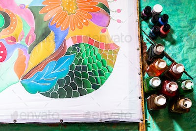 view of paints and silk canvas with floral batik