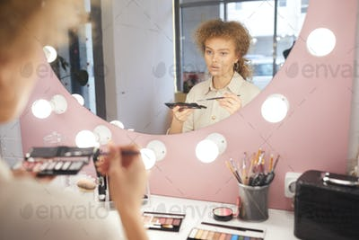 Young Woman Applying Make up by Mirror