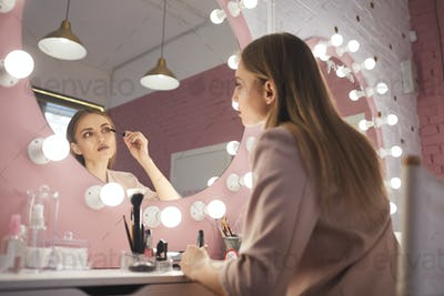Young Woman Looking in Mirror and Applying Make up at Dressing Table