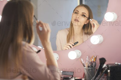 Beautiful Young Woman Looking in Mirror and Applying Make up
