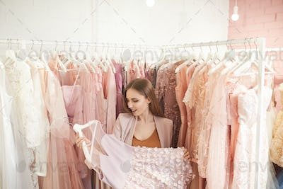 Woman Holding Beautiful Dress in Boutique