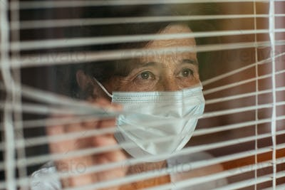 Close up of anxious old woman surgical mask looking through window blinds during self-quarantine.