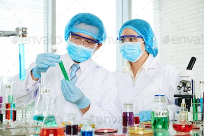 Scientist showing test-tube with green liquid to coworker