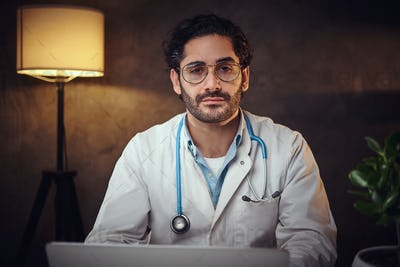 Young doctor in glasses at his office