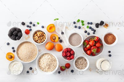 raw cereals, fruits and nuts for breakfast. Oatmeal flakes and steel cut, barley