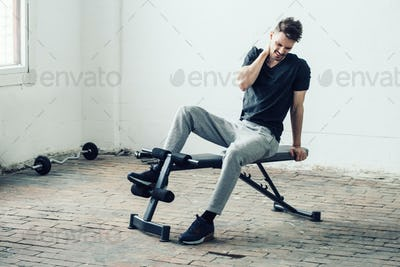 Man sport pain. Handsome guy in sport gym back pain and led