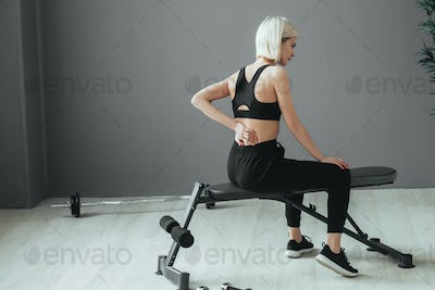 Sport pain. Woman in sport gym with ache. Sporty blonde female with sporty equipment.