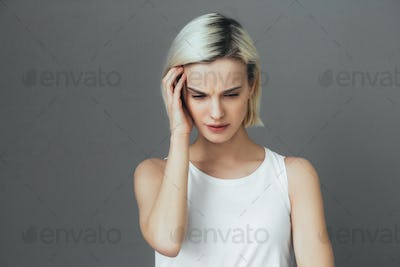 Headache woman portrait. Girl with pain head and neck  over gray wall