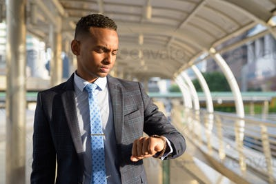 Young handsome African businessman in suit checking the time in the city