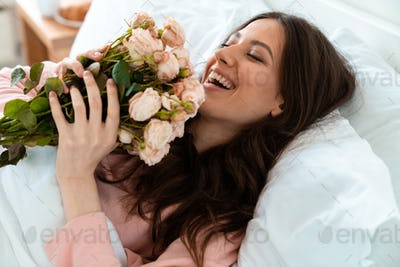 Pretty young woman in bed holding flowers.