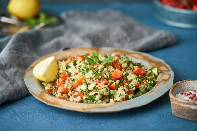 Tabbouleh salad with quinoa. Eastern food with vegetables mix, vegan diet. Side view, old plate