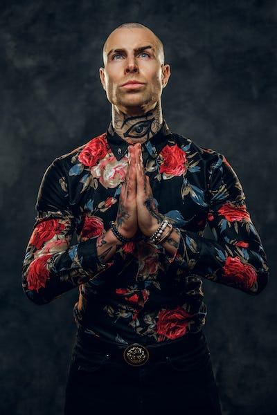 Elegant tattooed, bald fashionable male model posing in a studio