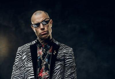 Fashionable tattooed male model posing in a studio