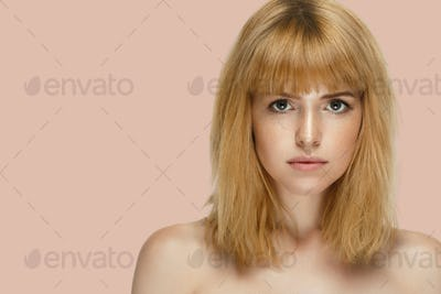 Beautiful woman face model face red hair on summer pink background.