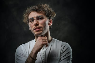 Portrait of a handsome casual guy with curly hair posing in the dark studio while thinking